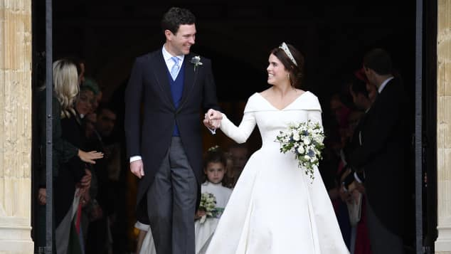 Jack Brooksbank and his wife Princess Eugenie exiting St. George's Chapel.