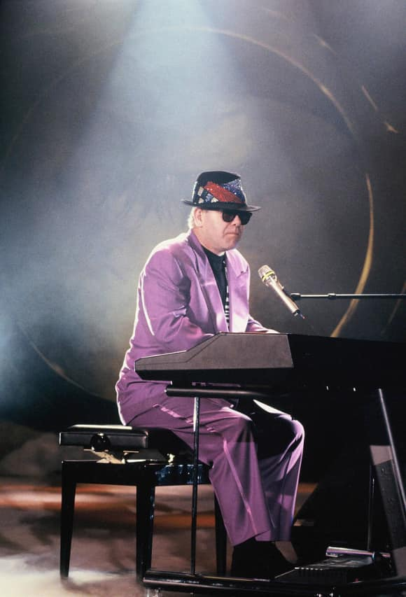 Elton John in a purple suit on the piano